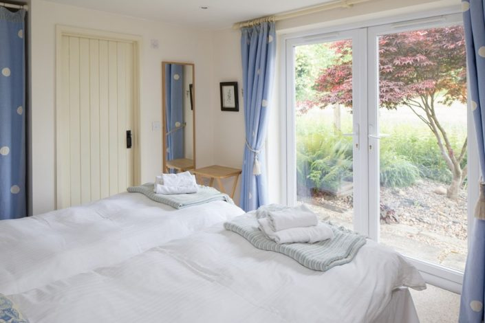 French doors from the ground floor bedroom open onto the garden with views across the fields (Bedroom 1).