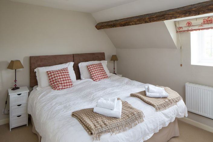 Bedroom 2 on the first floor has exposed beams, lovely throws and an en suite shower-room.
