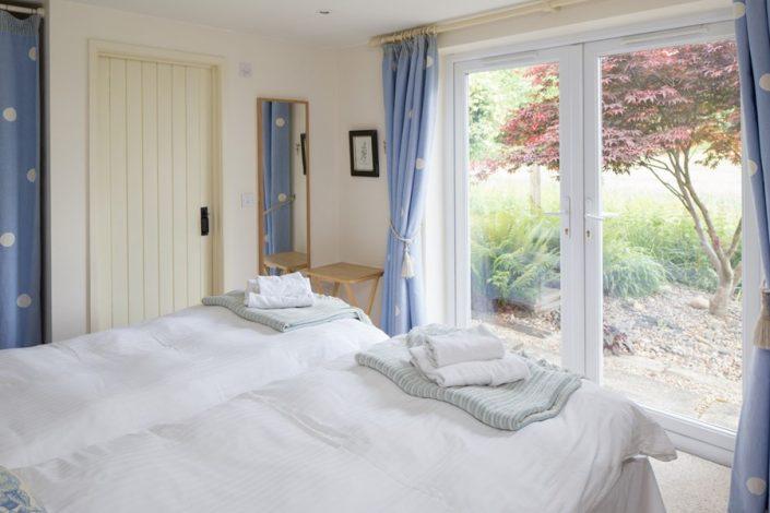 French doors from the ground floor bedroom open onto the garden with views across the fields (Bedroom 1).