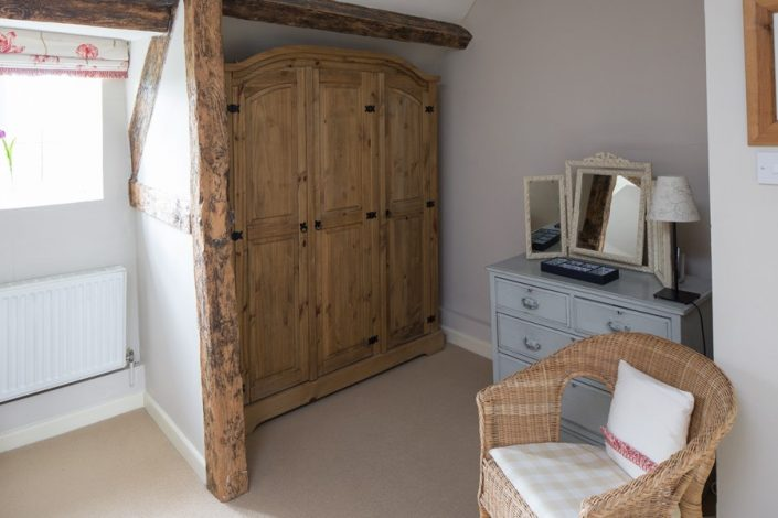 Bedroom 2 has real character; exposed beams create storage and a dressing-area.